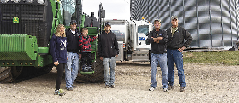 Family and delivery drivers standing in front of delivery truck and tractor