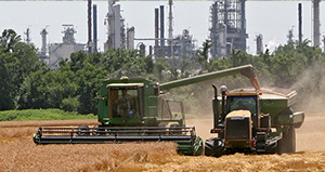 Farm equipment in field with refinery in background