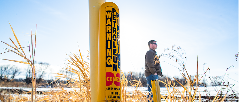 Farmer walking next to a buried pipeline warning post