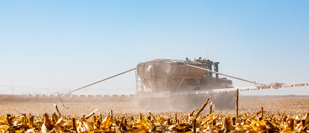A combine applying fertilizer in a farm field.