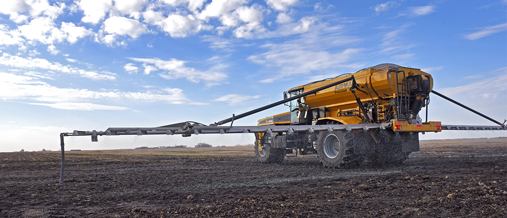 A combine applying fertilizer to a field in spring.