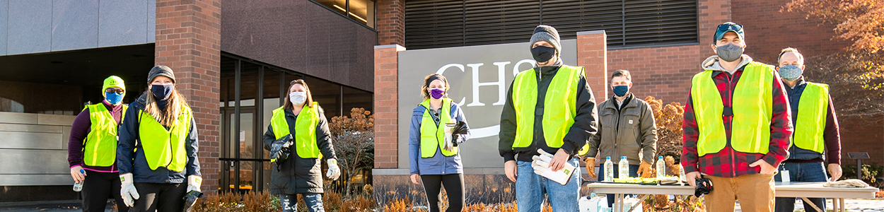 CHS employees wearing high-vis vests and facemaks standing physically distanced in front of CHS headquarters office building.