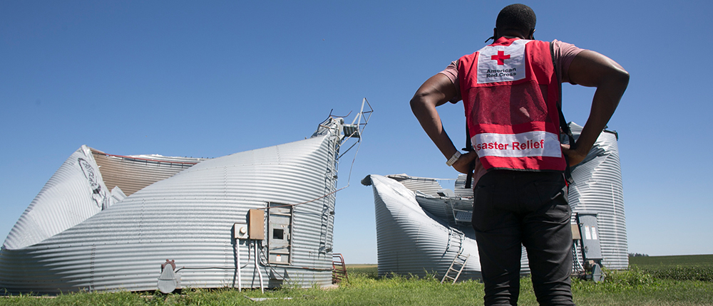 A Red Cross relief worker stands in front of a damaged grain bin.
