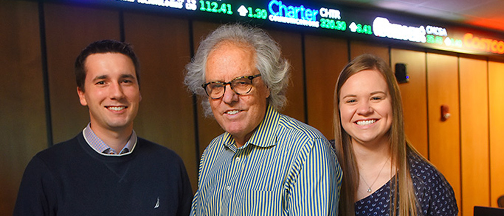 Jesse Klebe, left, and Jessica Fleck, right with professor William Wilson in the Commodity Trading Room