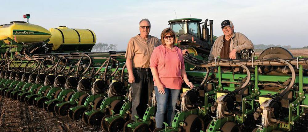 Zutz family next to their farm equipment