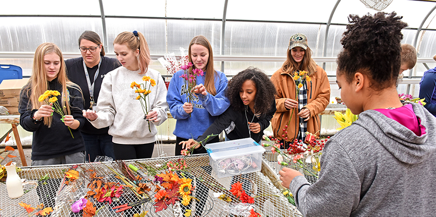 Students arranging flowers in greenhouse