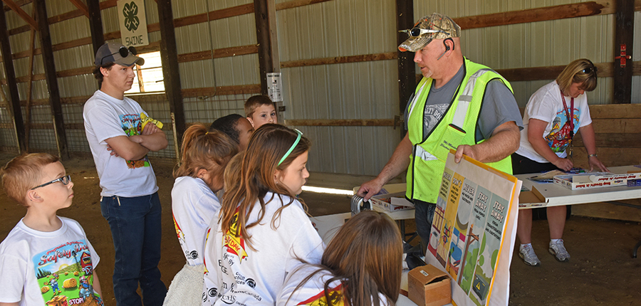 Children gathering around a table to learn about ag health and safety